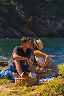 Romantische szene eines paares, das sich auf dem picknick in den bergen am meer küsst und die hitze genießt