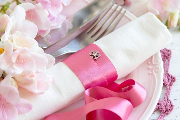 Romantische tabelleneinstellung mit freesienblumen und rosa band schließen oben