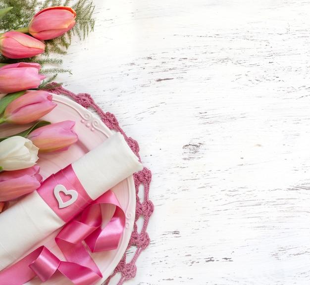 Romantische tabelleneinstellung mit tulpenblumen und rosa bandoberansicht mit kopienraum