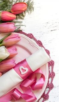 Romantische tabelleneinstellung mit tulpenblumen und rosa bandoberansicht