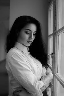 Romantische traurige brünette frau mit dem lockigen langen haar und einer tätowierung auf dem arm, der nahe dem fenster sitzt. studioaufnahme in schwarzweiß