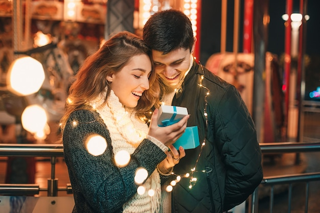 Romantische überraschung zu weihnachten, frau erhält ein geschenk von ihrem freund