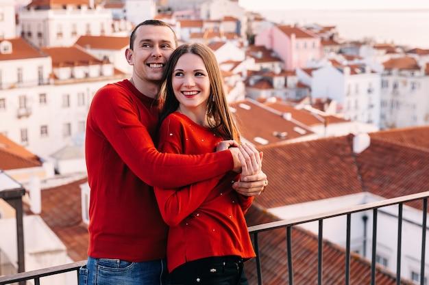 Romantische umarmung eines verliebten paares in roten sweatshirts und aufrichtigem lächeln. blick auf die stadt.