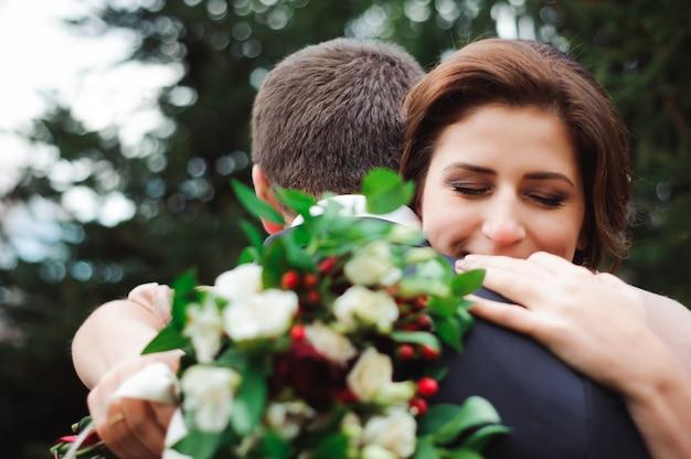Romantische umarmung von jungvermählten. paar geht in den park.