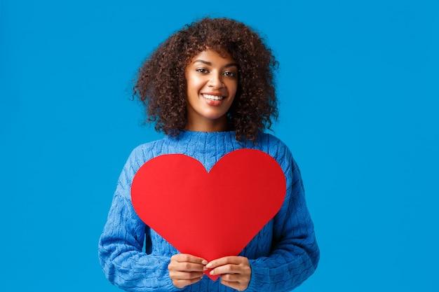 Romantische und sinnliche niedliche afroamerikanische frau mit afro-haarschnitt, die großes rotes herzzeichen hält und lächelt.
