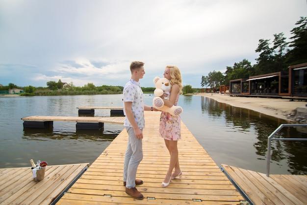 Romantische verabredungsüberraschung. ein junger mann und ein mädchen auf einem pier mit blick auf den see. der mann gibt dem mädchen einen teddybär.