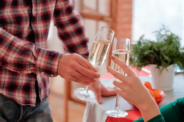 Romantische weihnachtsfeier. beschnittener schuss des paares, das champagnergläser über unscharfem festlichem tisch klirrt.
