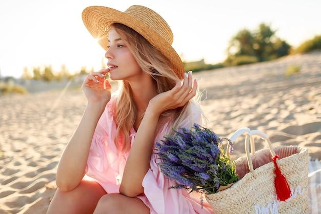 Romantische weiße frau im trendigen hut und im eleganten rosa kleid, das am strand aufwirft. strohsack und blumenstrauß haltend.