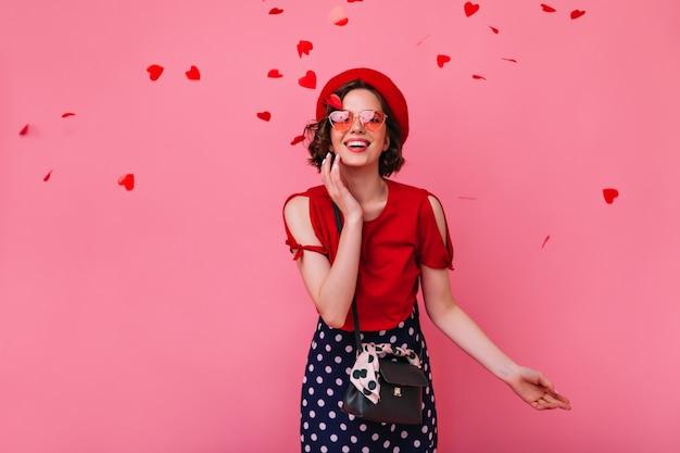 Romantische weiße frau mit braunem haar, das glück am valentinstag ausdrückt. bezauberndes stilvolles mädchen in den lustigen gläsern, die mit konfetti aufwerfen.