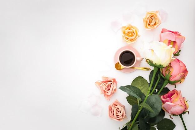 Romantische zusammensetzung mit rosen, den blumenblättern und rosa tasse kaffee mit kopienraum
