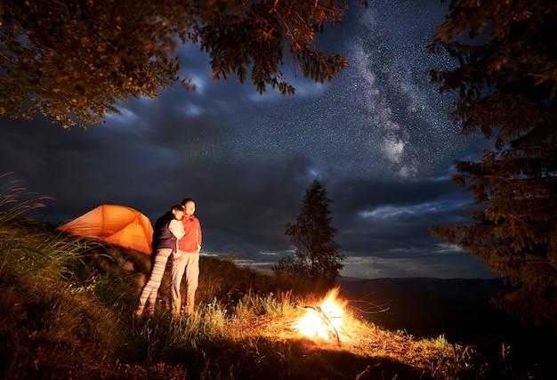 Romantischer abend eines jungen paares wanderer in den bergen am feuer unter dem sternenhimmel in der nacht auf dem campingplatz. junge volkstouristen, die nahe beleuchtetem orangefarbenem zelt stehen und das feuer betrachten.