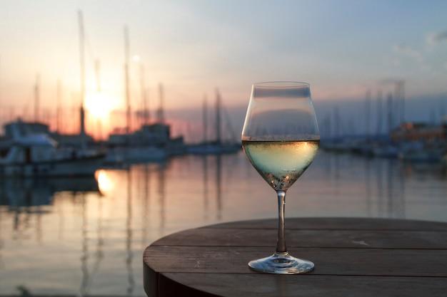 Romantischer abendsonnenuntergang mit nebligen glas weißwein im hintergrund meer und yachtclub