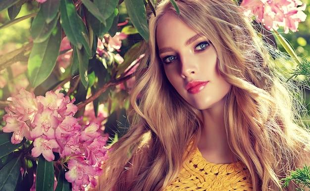 Romantischer blick der schönen blauen augen der jungen frau, umgeben von blühenden gartenblumenbäumen. langes blondes haar frei locken, elegantes make-up mit rosafarbenen lippen. blüte der jugend.