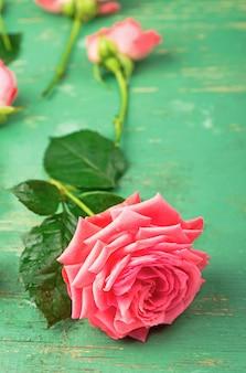 Romantischer blumenrahmenhintergrund rosa rosen auf hölzernem hintergrund.