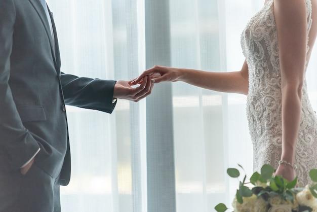 Romantischer bräutigam und braut, die hände halten, die am fenster stehen
