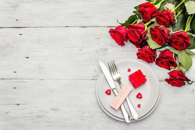 Romantischer esstisch. liebeskonzept für valentinstag oder muttertag, hochzeitsbesteck. strauß der frischen burgunderrosen, weißer weinleseholzbretterhintergrund