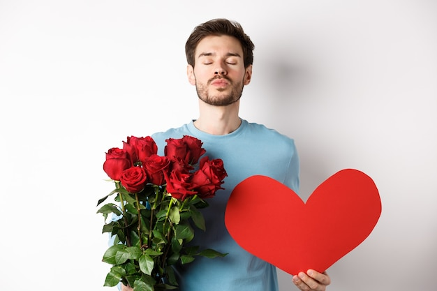 Romantischer freund, der auf kuss wartet, strauß rosenblumen und großes rotes herz am valentinstag hält, liebe in der luft, über weißem hintergrund stehend.