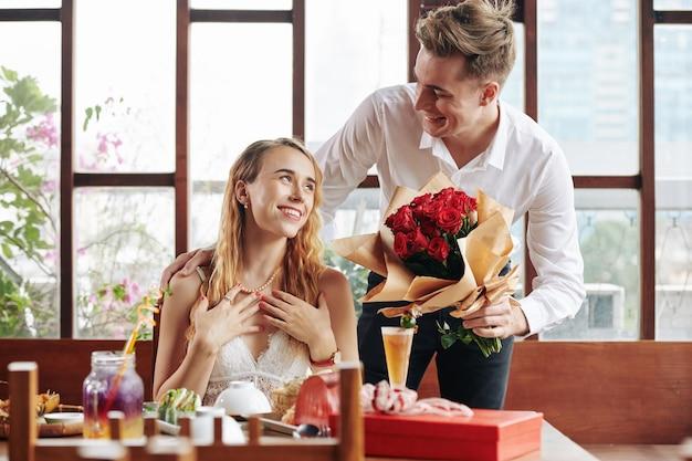 Romantischer freund, der dem mädchen rosen gibt