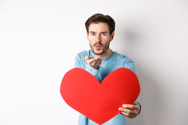 Romantischer freund, der luftkuss sendet und großes rotes valentinstagherz hält, auf weiß stehend
