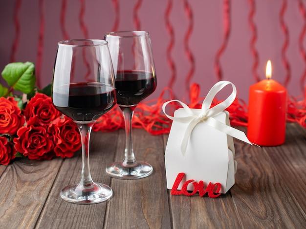 Romantischer gemütlicher abend mit wein, blumen, kerzen und geschenk