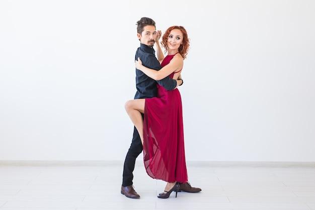 Romantischer, geselliger tanz, menschenkonzept - paar tanzt salsa oder kizomba oder tango auf weißer wand mit kopierraum