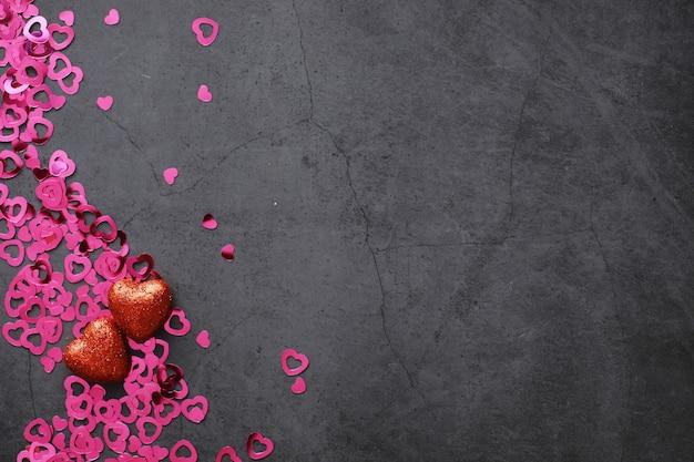 Romantischer hintergrund. das konzept der liebe und beziehungen. herzförmige figuren auf dunklem hintergrund. karte zum valentinstag.