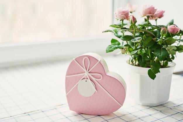 Romantischer hintergrund des valentinstags mit blumenrosen. valentinskarte mit kopierraum. blumen in geschenkbox. v.