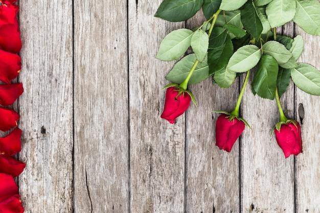 Romantischer hintergrund mit blühenden roten rosen auf hölzerner rustikaler tabelle mit copyspace.