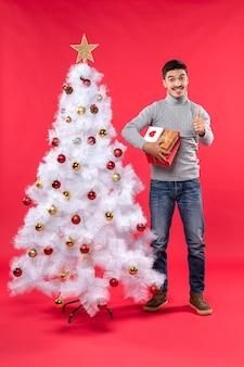 Romantischer hübscher erwachsener, der nahe dem geschmückten weißen weihnachtsbaum steht und seine geschenke auf rot hält