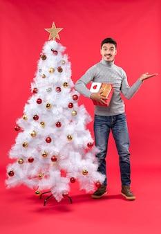 Romantischer hübscher erwachsener in einer grauen bluse, die nahe dem geschmückten weißen weihnachtsbaum steht