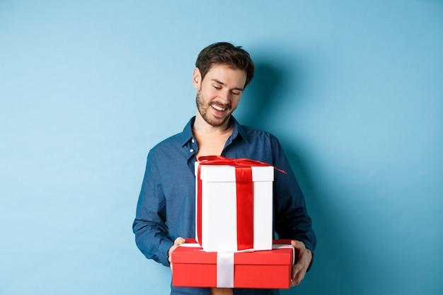 Romantischer junger mann mit bart, der geschenkboxen am valentinstag glücklich betrachtet, geschenke an liebhaber gibt, über blauem hintergrund stehend.