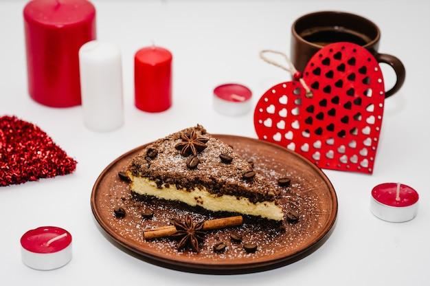 Romantischer kuchen mit kaffee. verzierte rote herzen auf einem weißen holztisch.
