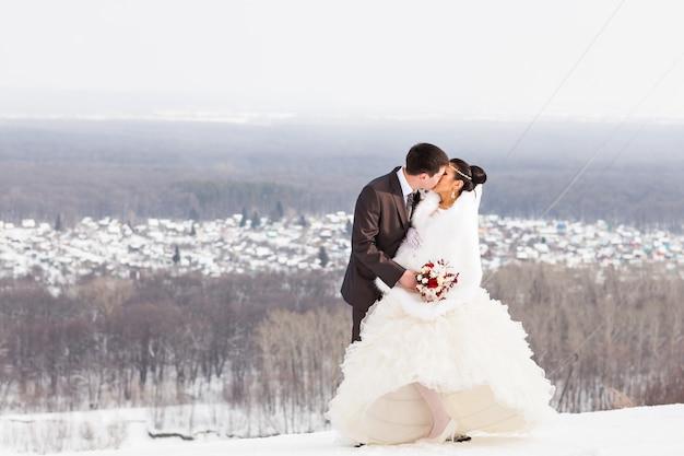 Romantischer kuss glückliche braut und bräutigam am winterhochzeitstag