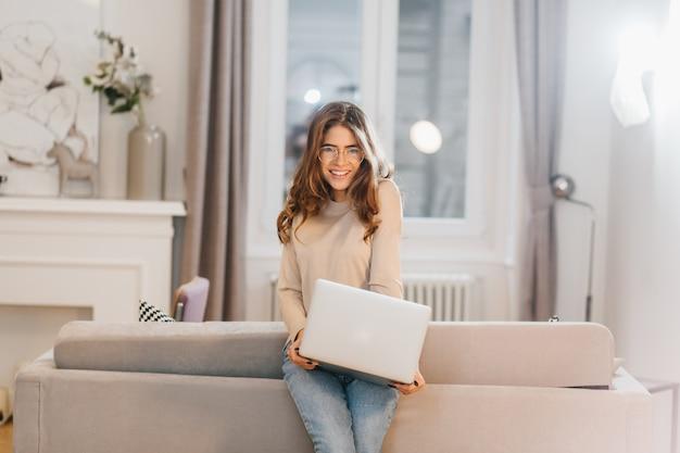 Romantischer lächelnder student in den gläsern, die zu hause mit computer aufwerfen