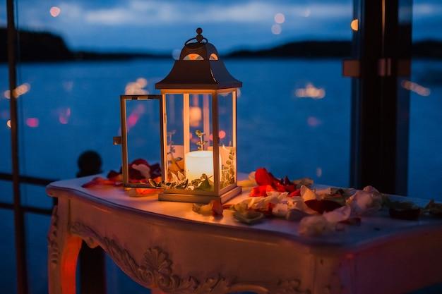Romantischer luxusabend mit champagner-ambiente mit zwei gläsern rosenblättern und kerzen