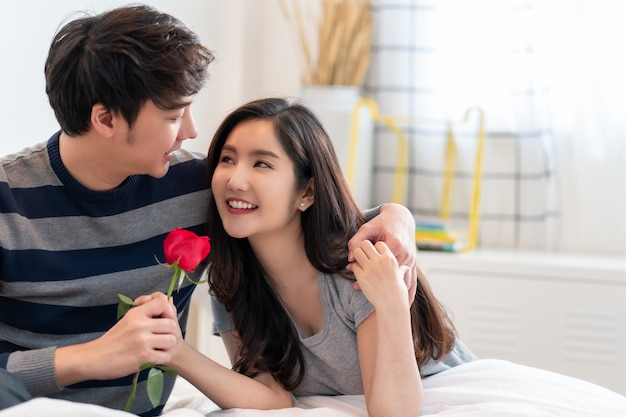 Romantischer mann, der der schönen frau eine rose gibt, schönes elegantes asiatisches paar umarmt und lächelt im schlafzimmer.