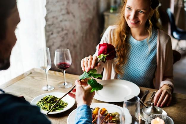 Romantischer mann, der einer frau eine rose an einem datum gibt