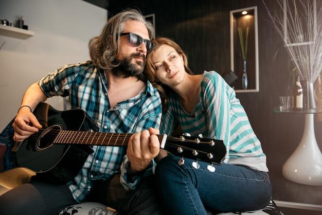 Romantischer mann, der gitarre für seine frau spielt