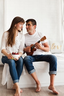 Romantischer mann, der ukulele spielt und seine frau hält schüssel erdbeeren betrachtet