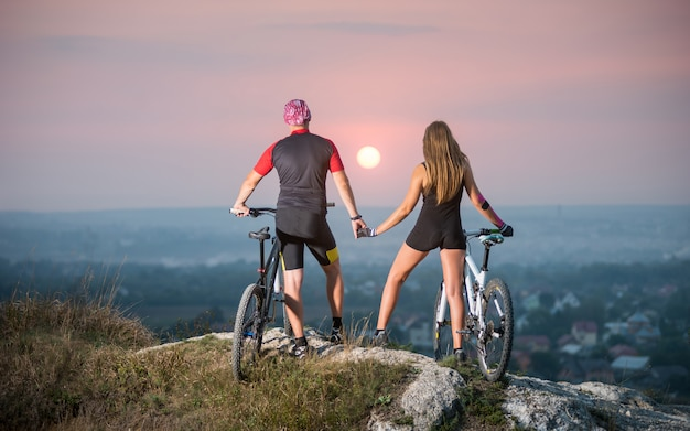 Romantischer radfahrer mit den mountainbikes, die auf die oberseite eines hügels stehen