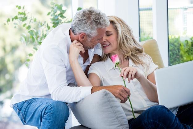 Romantischer reifer mann, der der frau rose gibt