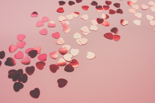 Romantischer rosa festlicher hintergrund mit rotem herzförmigem konfetti