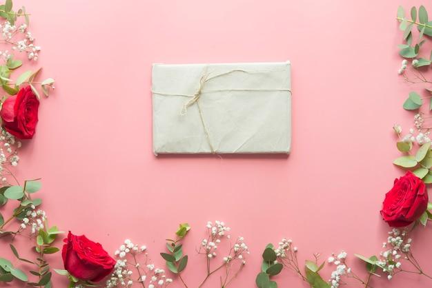 Romantischer rosa hintergrund mit dem rahmen gemacht von den blumen und vom geschenk der roten rosen