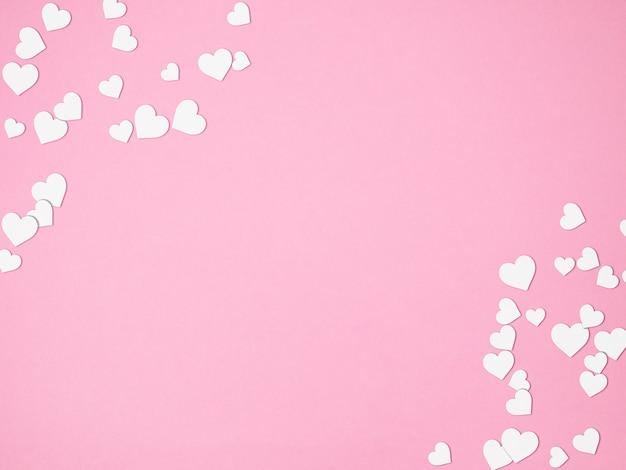 Romantischer rosa hintergrund mit weißen herzen und kopienraum, valentinstag, draufsicht