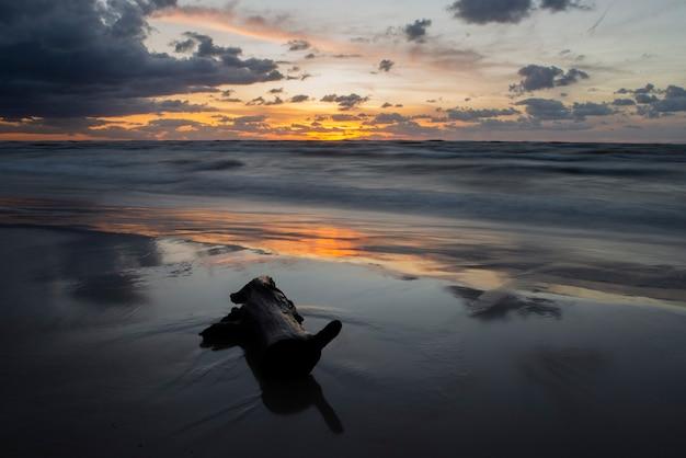 Romantischer sonnenuntergang am strand mit holz auf dem sand