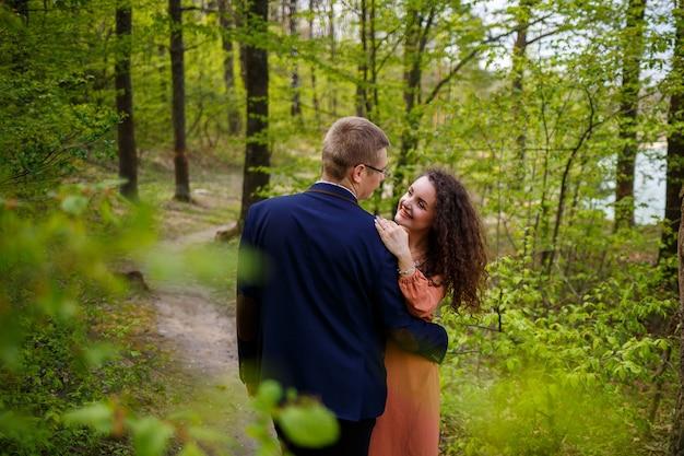 Romantischer spaziergang eines jungen paares in einem grünen wald, warmes frühlingswetter. kerl und mädchen umarmen sich in der natur
