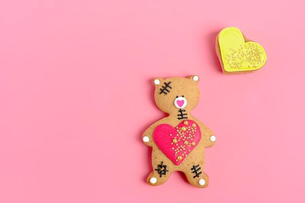 Romantischer teddybär, lebkuchenherz auf modischem rosa hintergrund.