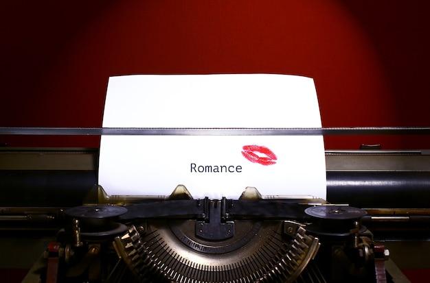 Romantischer titel oder überschrift in schwarzer tinte auf weißem papier auf vintage-handschreibmaschine getippt. roter lippenstiftdruck auf papier.