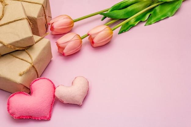 Romantischer tulpenstrauß auf rosa tisch mit herzen und geschenken. valentinstag konzept