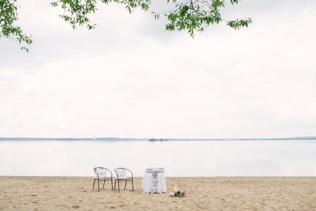 Romantisches abendessen am seeufer für ein verliebtes paar oder ein brautpaar: einen tisch und zwei stühle